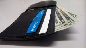 wallet with money coming out of it