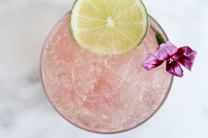 Fruity cocktail with a lime and flower