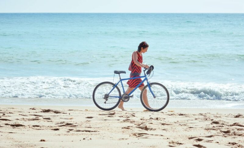 girl with a blue bike on the beach